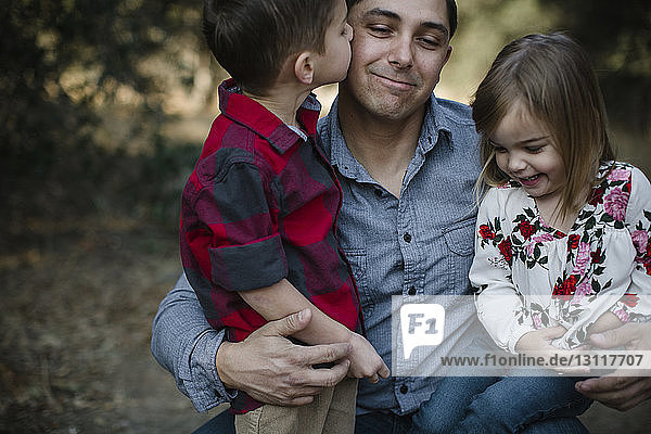 Loving boy kissing father while sister sitting on his lap