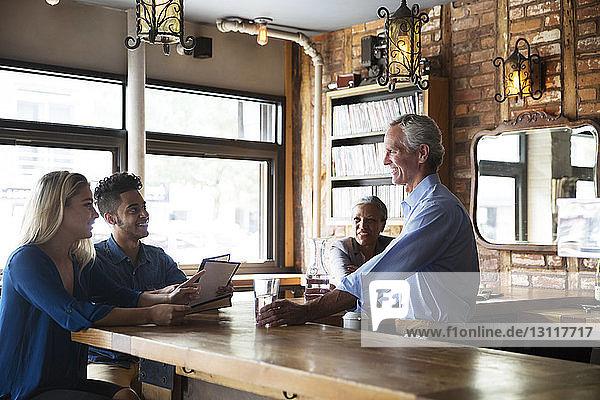 Männlicher Besitzer serviert Getränke  während er sich mit Kunden an der Bartheke im Café unterhält