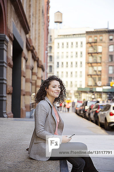 Seitenansicht einer nachdenklichen Geschäftsfrau  die auf dem Bürgersteig sitzt