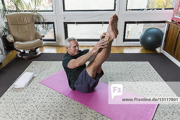 Reifer Mann übt zu Hause auf der Gymnastikmatte