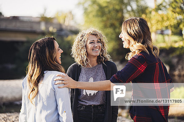 Happy female friends talking standing outdoors
