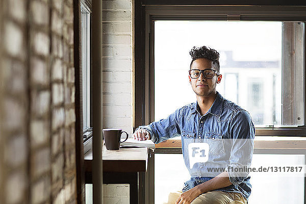 Portrait of young man with book at table sitting against glass windows at cafe