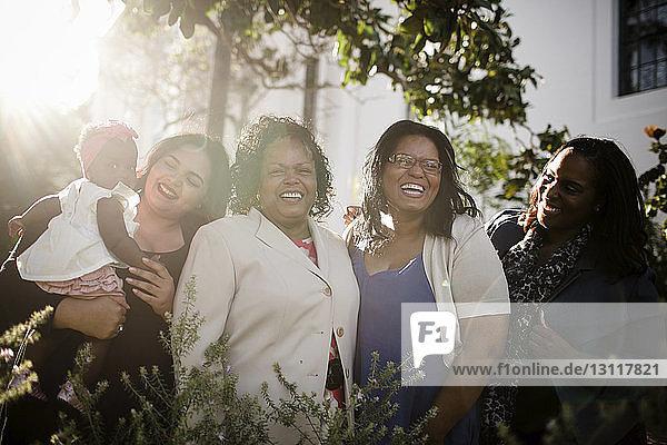 Glückliche Familie steht inmitten von Pflanzen im Park