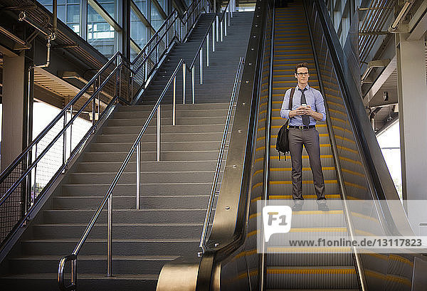 Low angle view of businessman standing on escalator