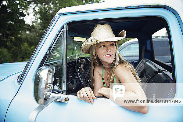 Woman looking away while sitting in pick-up truck
