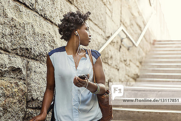 Woman looking away while listening music to steps