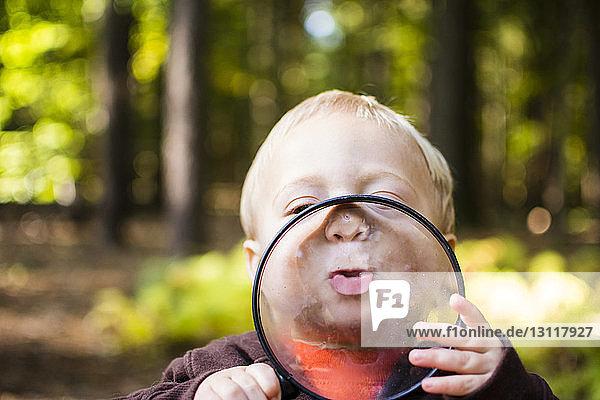 Nahaufnahme eines Jungen  der im Wald steht und eine Lupe hält