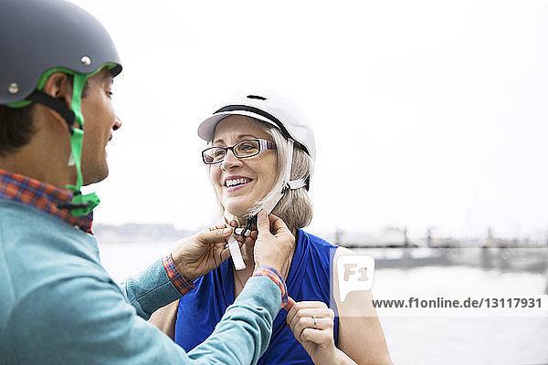 Reifer Mann hilft Frau beim Tragen eines Fahrradhelms bei klarem Himmel