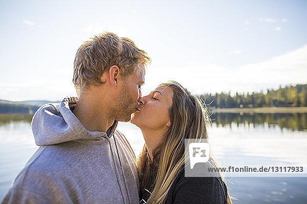 Liebespaar küsst sich auf Mund gegen See