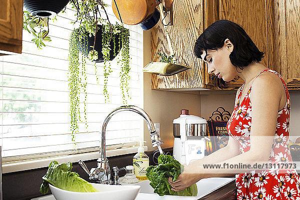 Seitenansicht einer Frau  die Salat in der Küchenspüle wäscht