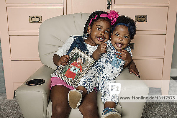 Portrait of happy sisters with picture frame sitting on chair by cabinet at home