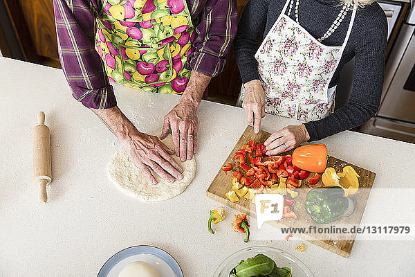 Mitschnitt einer Frau  die Paprika schneidet  während ein Mann zu Hause in der Küche Pizzateig herstellt