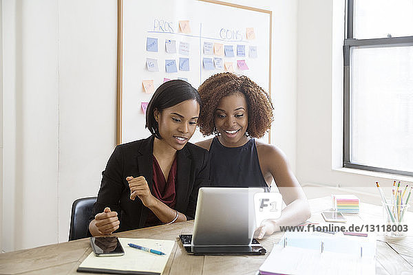 Glückliche Geschäftsfrauen mit Tablet-Computer im Sitzungssaal