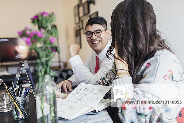 Lächelnde Geschäftskollegen am Schreibtisch im Büro