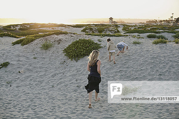 Rear view of mother and sons running at beach