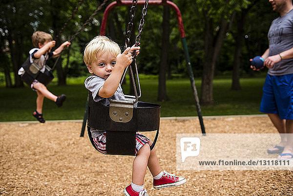 Niedrige Sektion eines Vaters mit Kindern  die auf dem Spielplatz schaukeln
