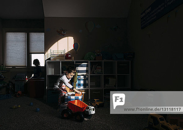 Boy picking toy from container at home