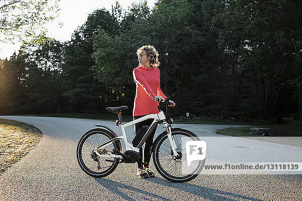 Woman looking away while standing by mountain bike at country road