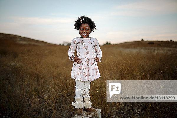 Porträt eines lächelnden Mädchens  das auf einem Grasfeld gegen den Himmel im Wald steht