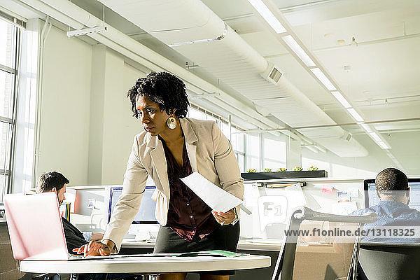 Geschäftsfrau benutzt Laptop-Computer  während Geschäftsleute im Hintergrund arbeiten