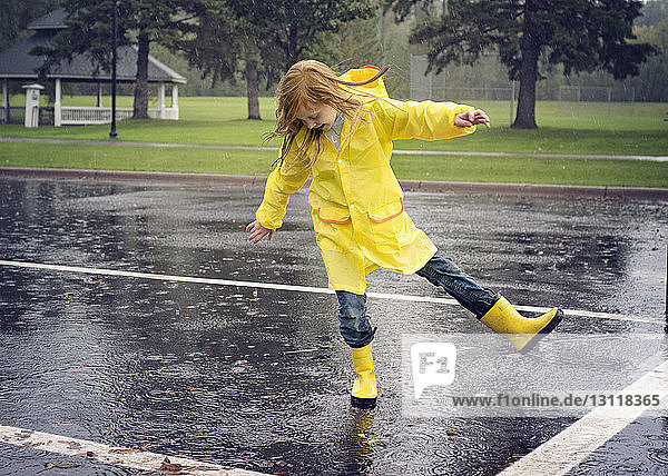 Playful girl wearing raincoat while dancing on road during rainfall