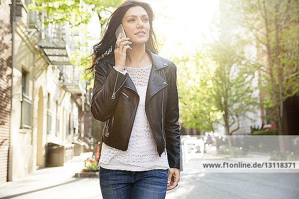Schöne Frau nimmt beim Gehen auf der Straße ein Smartphone entgegen