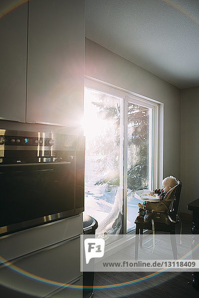 Side view of boy having food while sitting on high chair by window at home