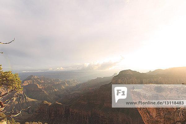 Mann betrachtet Aussicht  während er auf Bergen gegen den Himmel sitzt