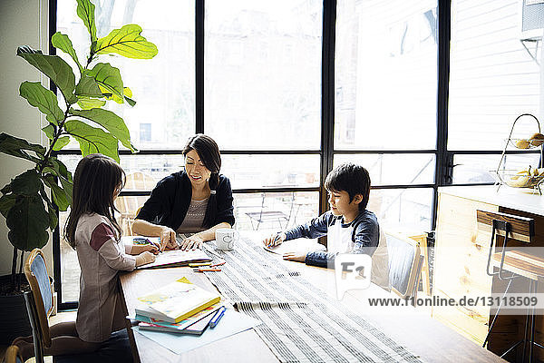 Mother teaching children on table against window at home