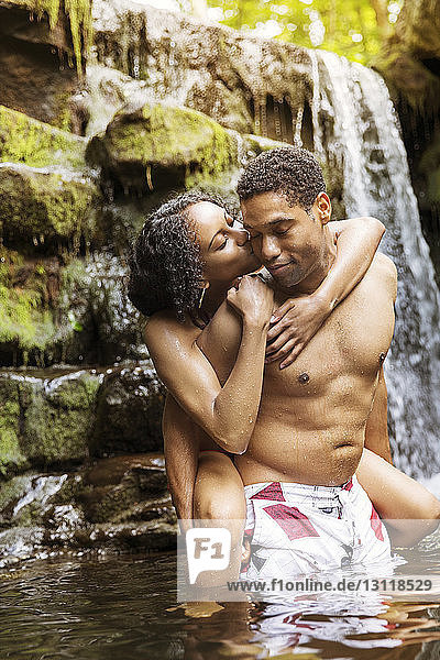 Man piggybacking woman kissing in river by waterfall