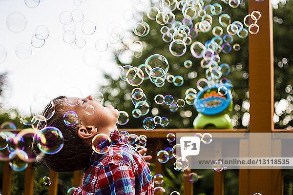 Glücklicher Junge genießt Blasen  während er auf der Veranda steht