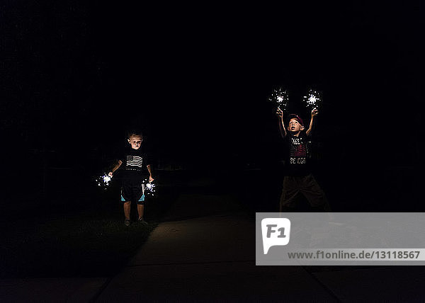 Boys playing with sparklers at night