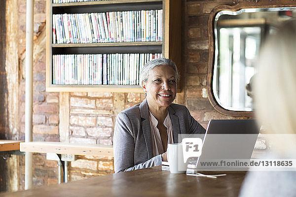 Lächelnde Frau mit Laptop,  während sie im Café am Bücherregal sitzt