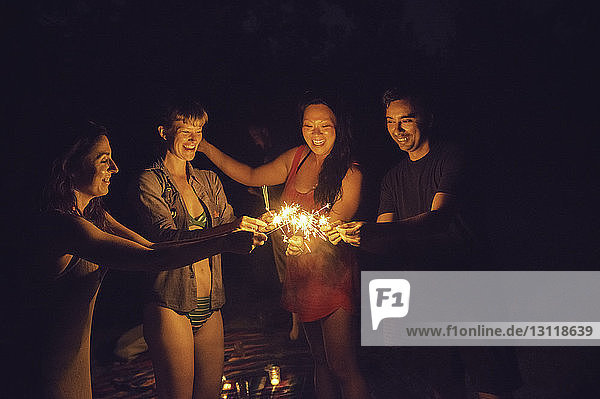 Friends playing with sparklers at night