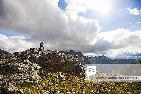 Hiker climbing on rocks against cloudy sky