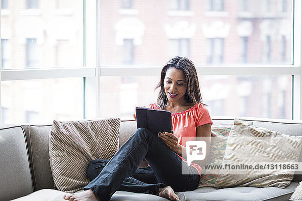 Woman using tablet computer while sitting on sofa against window at home