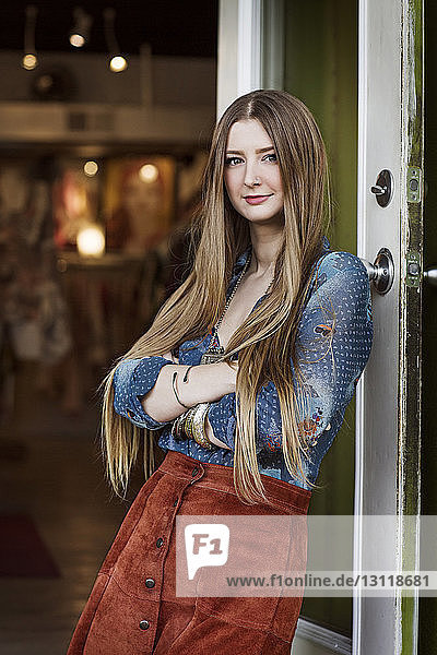 Portrait of woman with arm crossed leaning on boutique entrance