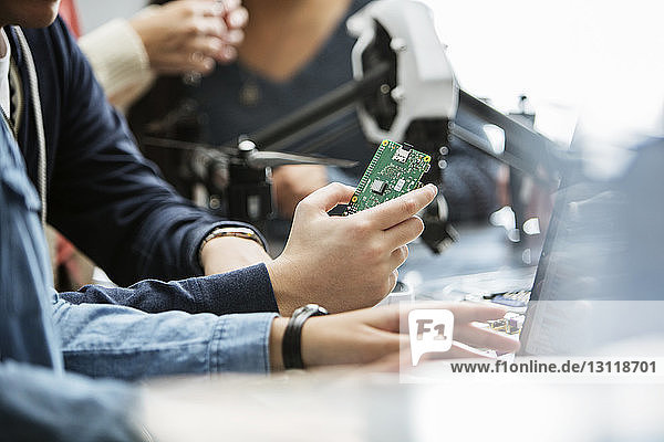 Cropped image of students holding circuit board in classroom
