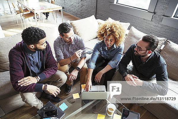Geschäftsfrau diskutiert mit Kollegen  während sie im Büro auf dem Sofa sitzt