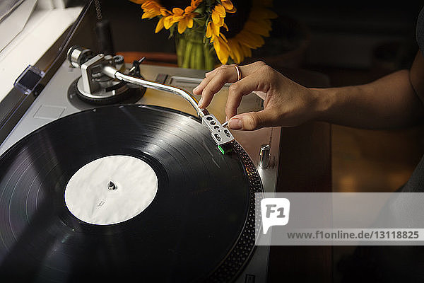 Cropped hand of woman playing music on turntable at home