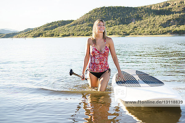 Smiling woman with paddleboard walking in lake on sunny day