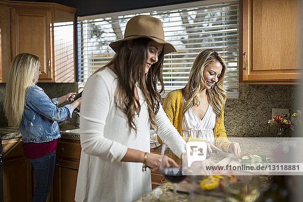 Lächelnde Freunde  die zu Hause Essen zubereiten