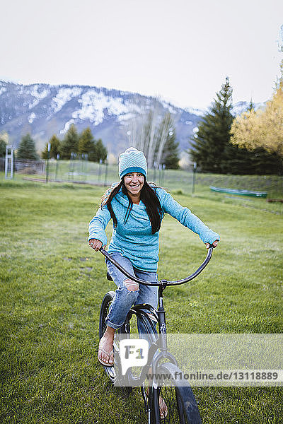 Portrait of woman riding bicycle on grassy field against mountain at park