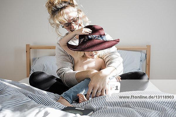 Glückliche Mutter mit hemdloser Tochter mit Hut  die zu Hause auf dem Bett sitzt