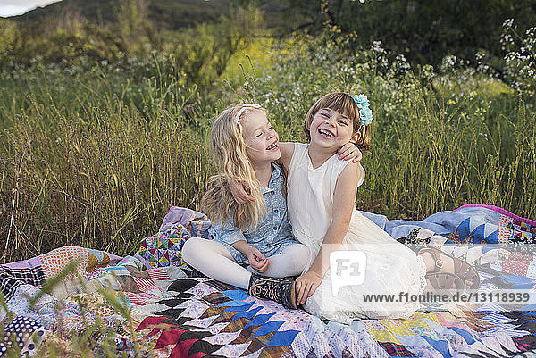 Cheerful sisters sitting on blanket in park