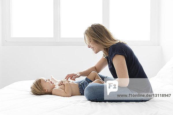 Glückliche Mutter spielt mit hemdloser Tochter  die zu Hause auf dem Bett liegt