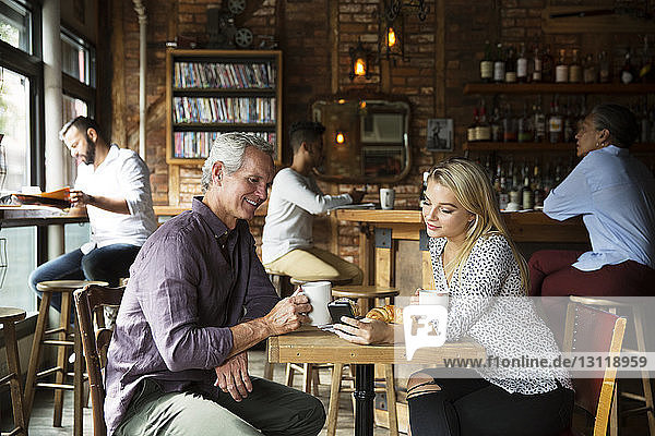 Woman showing phone to man while customers relaxing at cafe