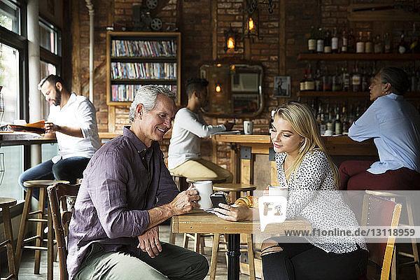 Frau zeigt Mann Telefon  während sich Kunden im Café entspannen
