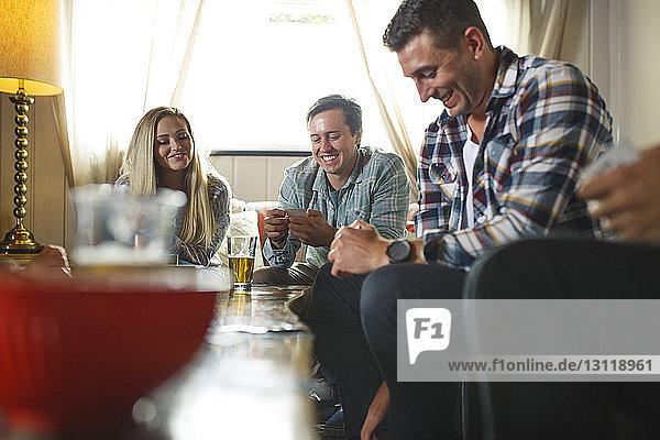 Lächelnde Freunde beim Kartenspiel beim geselligen Beisammensein zu Hause
