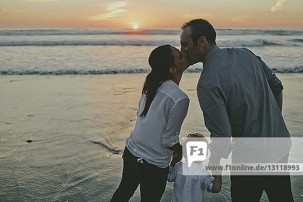 Couple kissing while holding hands of son at beach during sunset